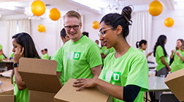 Employees wearing green shirts while packing boxes.